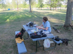 Me: writing while cooking dinner while camping during a motorcycle trip (with dogs and husband) through Canada to Vermont. I am the QUEEN of doing it all - or too much?!